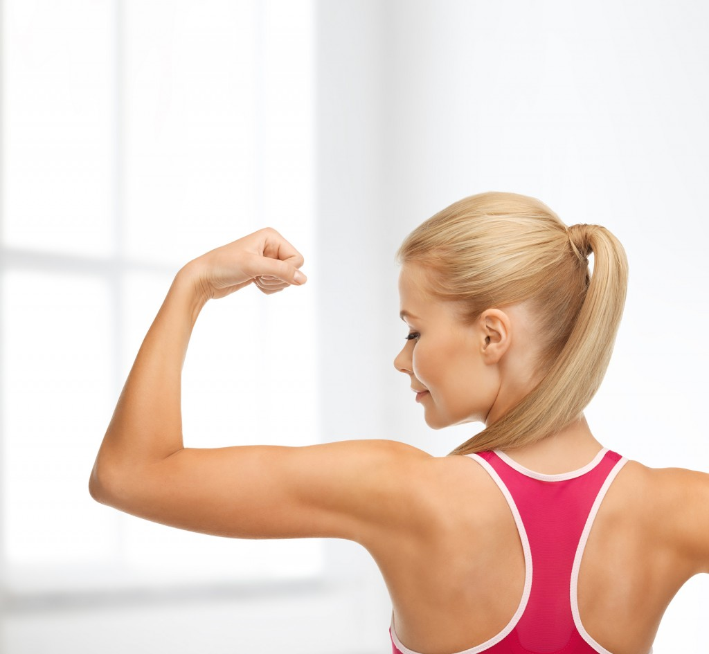 fitness and home concept - young sporty woman showing her biceps
